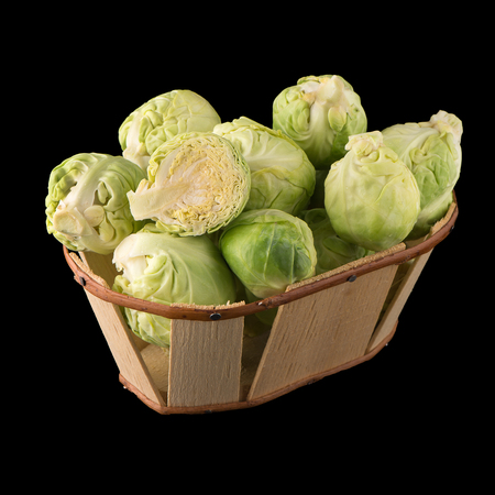 grocer: Fresh brussels sprouts and wooden baslet isolated on black background.