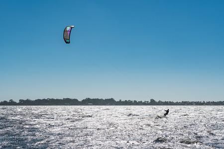 kiteboarding: Kiteboarder enjoy surfing on a sunny day.