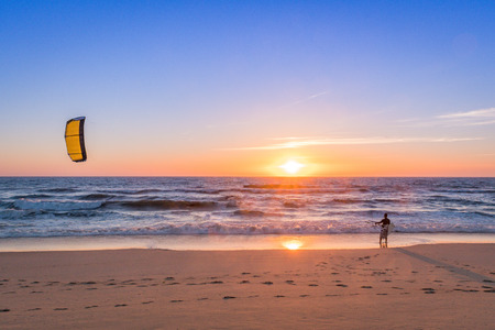kiteboarding: Kite surfer watching the waves at sunset in Portugal. Stock Photo