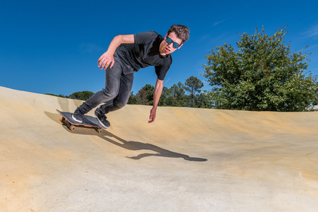 Skateboarder practice on a pump track park on a sunny summer day.