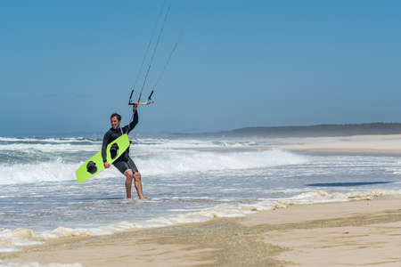 Kiteboarders enjoying surfing on a sunny day. Stock Photo