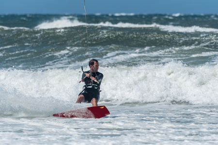 towed: Kiteboarder enjoy surfing on a sunny day.