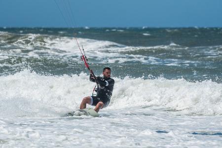 Kiteboarder enjoy surfing on a sunny day.