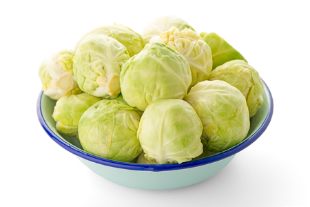 Fresh brussels sprouts on blue metal bowl isolated on white background.