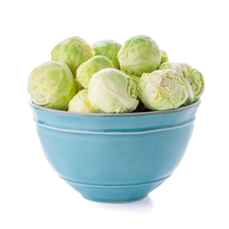 Fresh brussels sprouts on blue ceramic bowl isolated on white background. Stock Photo