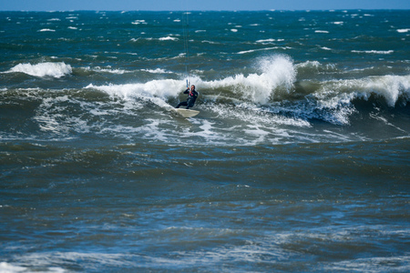 Kitesurfer riding ocean waves on a bright sunny day. Stock Photo