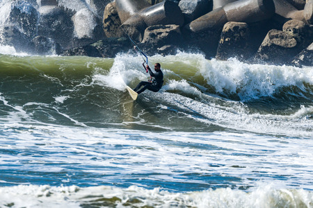 kiter: Kitesurfer riding ocean waves on a bright sunny day. Stock Photo