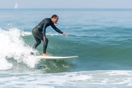 Surfer in action with a small action camera on the ocean waves on a sunny day.
