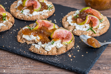 Canape or crostini with multigrain  crispread with cream cheese and fig jam on a slate board. Delicious appetizer ideal as an aperitif.