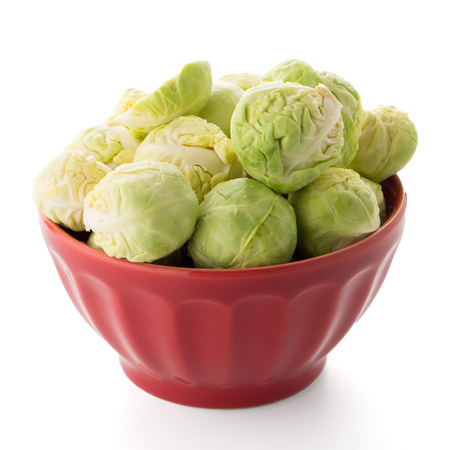 Fresh brussels sprouts on red ceramic bowl isolated on white background. Stock Photo