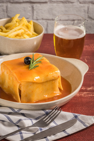 Traditional Portuguese snack food. Francesinha sandwich of bread, cheese, pork, ham, sausages, with tomato beer sauce and French fries. With beer and potatoes. On table.
