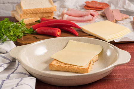 Ingredientes preparations of traditional Portuguese snack food. Francesinha sandwich of bread, cheese, pork, ham, sausages. On table. Imagens