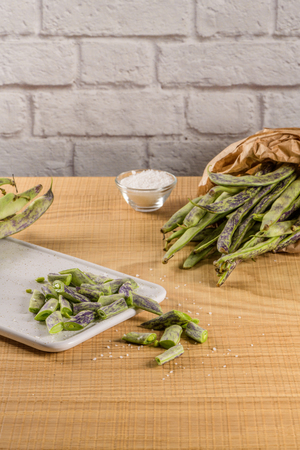 Heap of green beans on a rustic wooden table top view. Cutting board with green beans