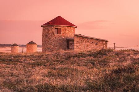 Old traditional wind-mills in sand-hills of Apulia Portugal. 版權商用圖片