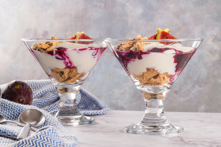 Figs pudding parfait with yogurt, blueberry jam, figs, hazelnut, and cookies in glass on white marble background. Stock Photo
