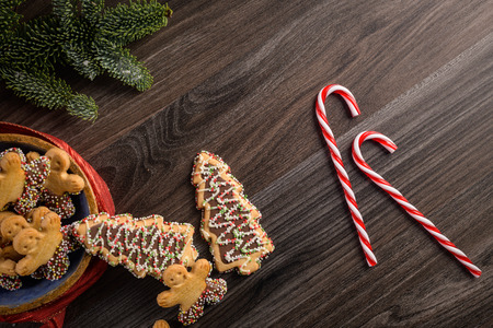 Christmas holiday background with gingerbread cookies, candy canes and evergreens over wooden table. Christmas and New year food. Christmas decoration and sweets on wood background.