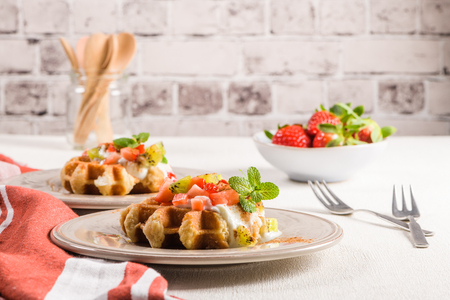 Fresh egg waffles dessert for breakfast with yogurt, strawberries and kiwi.