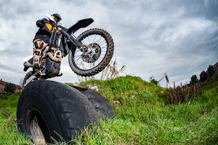Enduro bike rider in action. Obstacle overcome on mud and grass terrain. Imagens