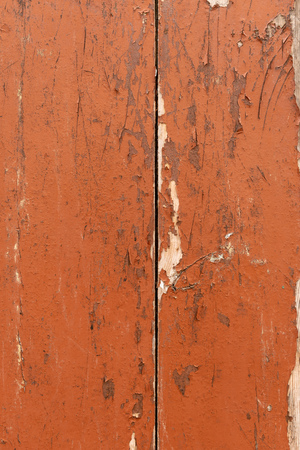 Grungy brown paintwork on a wooden panel