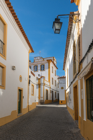 The view of narrow paved street of Evora with the cozy white houses. Evora. Alentejo. Portugal Stockfoto