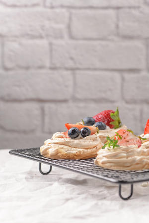 Small pavlova cakes with fresh raspberries and blueberries. Stockfoto