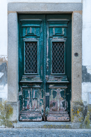 Old typical green painted wood Portuguese door. Фото со стока
