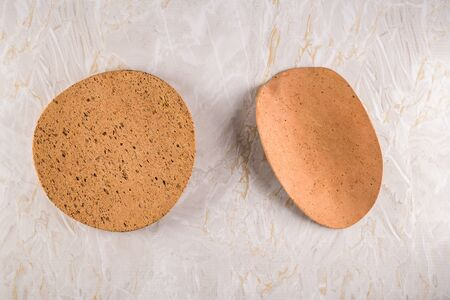 Top view of Two cork plates on a gray marble background with space for text.