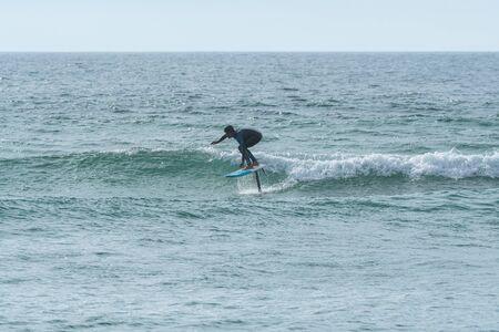 Un hombre de mediana edad haciendo surf en foil o en hidroala en el mar.