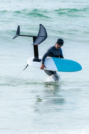 A middle aged man is finishing some foil surfing or hydrofoil surf training in the sea. Фото со стока