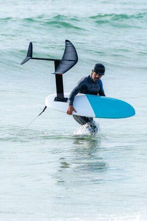 Un hombre de mediana edad está terminando un entrenamiento de foil surf o hidroala en el mar.