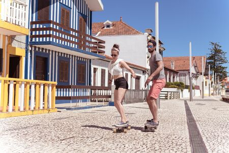 Young active couple enjoying a summer sunny day skateboarding near typical Costa Nova houses in Aveiro - Portugal.