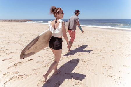 Couple of surfers with surfboards walking at a sandy beach.