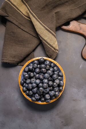 Fresh blueberries in ceramic bowl and brown cloth on dark table, rustic style.