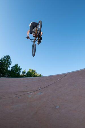 Biker jump high from jump box ramp performing 360 trick. Reklamní fotografie