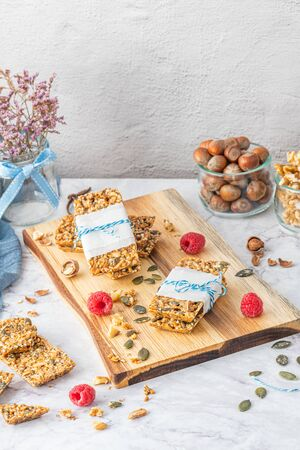Organic homemade granola bars on rustic marble stone kitchen countertop.