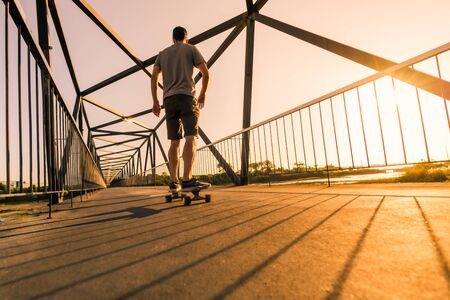 Young skateboarder speed through the pedestrian walkway Bridge at sunset.