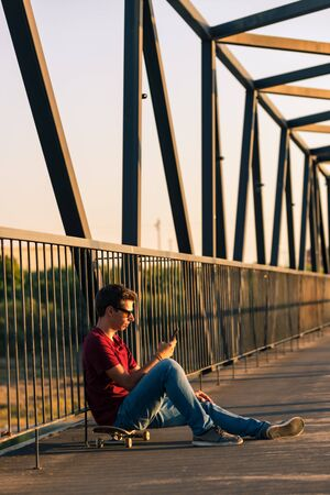 Young man sitting on his skateboard outside on a pedestrian bridge by the river, texting.