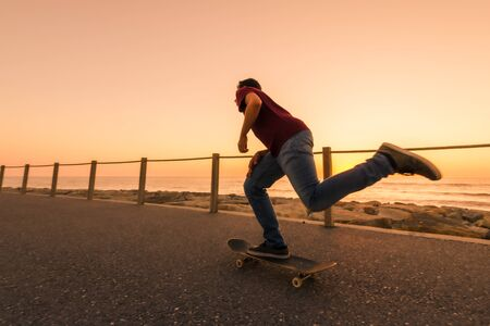 Skater training in the park near the sea in sunset.