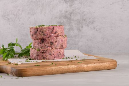 Raw veggie burger with beetroot and white beans with parsley leaves on wood cutting board.