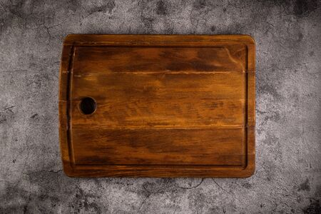 Top view of wooden cutting board on old stone countertop.
