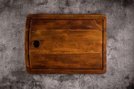 Vue de dessus d'une planche à découper en bois sur un vieux comptoir en pierre.