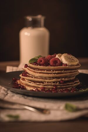 Pancakes with raspberries, banana slices, pomegranate seeds and honey on wooden vintage table. Stok Fotoğraf - 133864479