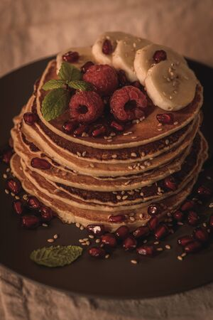 Pancakes with raspberries, banana slices, pomegranate seeds and honey on wooden vintage table. Stok Fotoğraf - 133864489