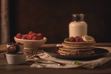 Pancakes with raspberries, banana slices, pomegranate seeds and honey on wooden vintage table.