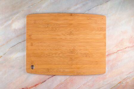 Draufsicht auf Holzschneidebrett auf grauem Marmorhintergrund mit Platz für Text. Standard-Bild