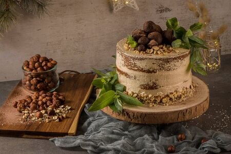 Delicious coffee and hazelnuts cake on table rustic wood kitchen countertop.