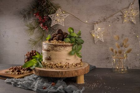 Delicious naked coffee and hazelnuts cake on table rustic wood kitchen countertop. Standard-Bild - 134846003