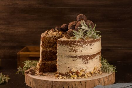 Slice of delicious naked coffee and hazelnuts cake on table rustic wood kitchen countertop. Standard-Bild - 134846004
