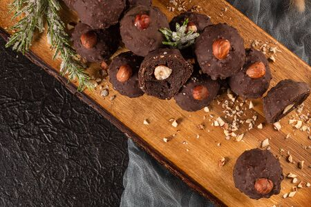 Dark chocolate truffles with hazelnuts over wooden cutting board. Standard-Bild - 134846010
