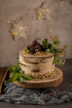 Delicious naked coffee and hazelnuts cake on table rustic wood kitchen countertop. Standard-Bild - 134846015